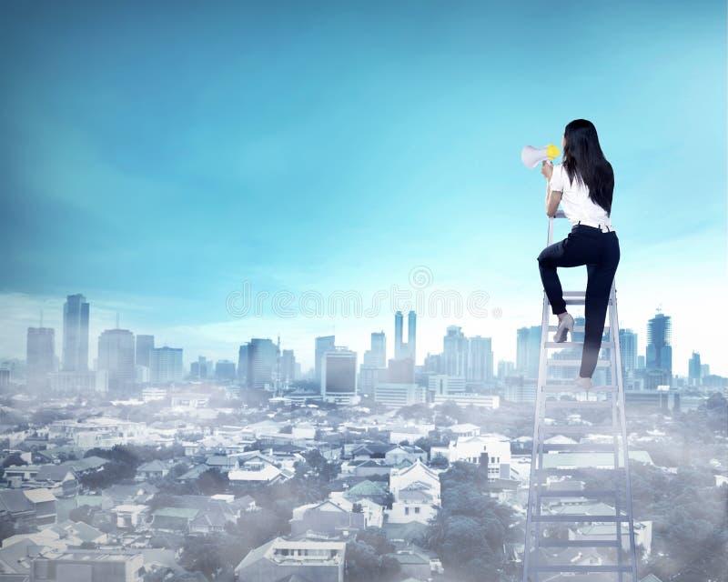 Бизнес-леди стоя на лестнице высокой и окрике с мегафоном стоковое изображение