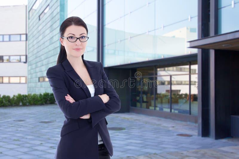 Бизнес-леди стоя на улице против офисного здания стоковое изображение