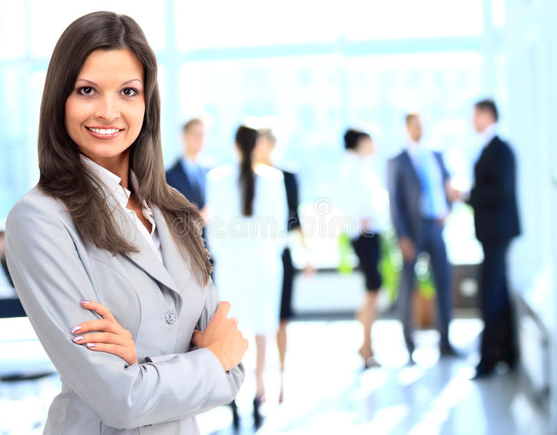 Бизнес-леди стоя с ее штатом в предпосылке на офисе стоковые фотографии rf