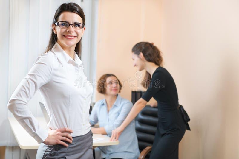Бизнес-леди стоя с ее штатом в предпосылке стоковые фотографии rf