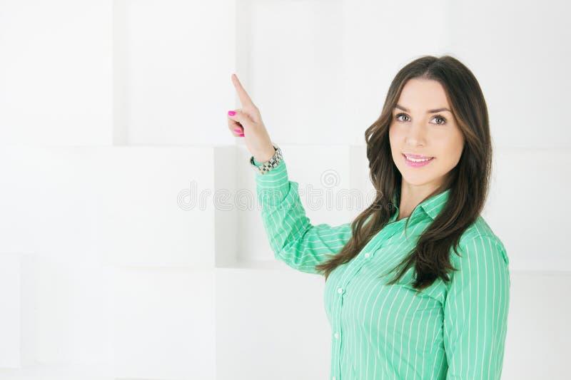 Бизнес-леди указывая на космос экземпляра на белой предпосылке стоковое фото