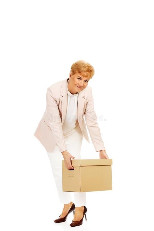 Бизнес-леди улыбки пожилая держа картонную коробку стоковое изображение rf