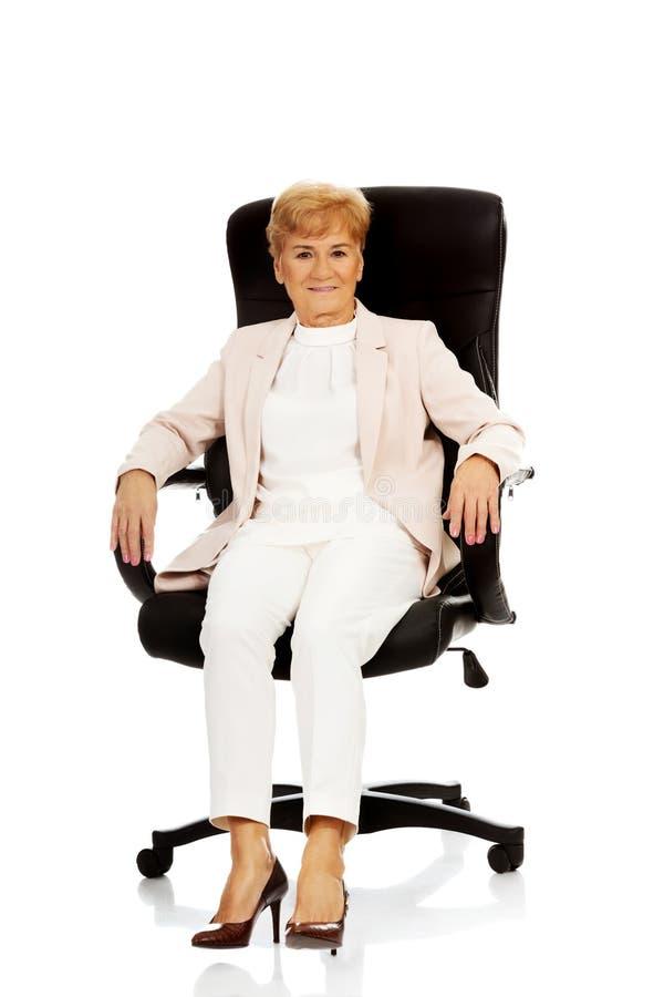 Бизнес-леди улыбки пожилая сидя на кресле стоковая фотография