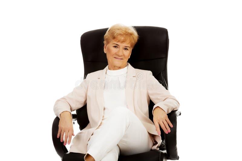 Бизнес-леди улыбки пожилая сидя на кресле стоковые фото