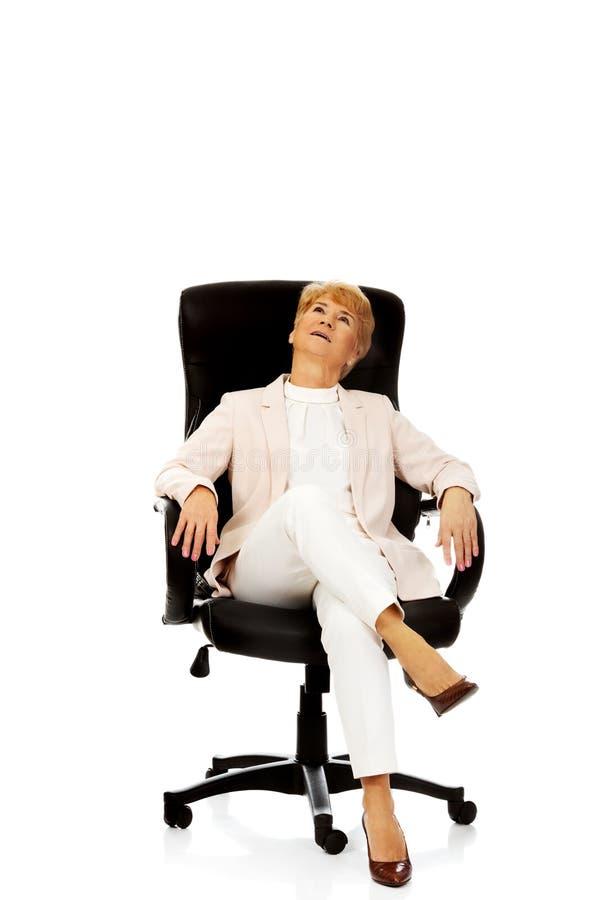 Бизнес-леди улыбки расслабляющая пожилая сидя на кресле стоковая фотография rf