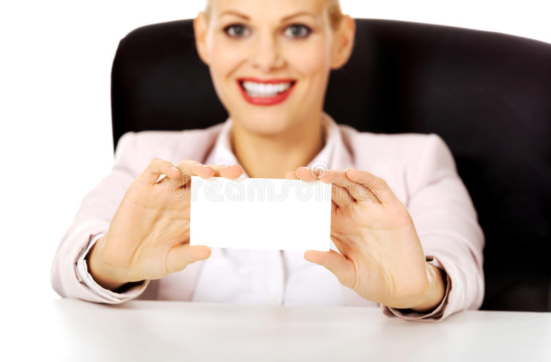 Бизнес-леди улыбки сидя за столом и держа пустую визитную карточку стоковая фотография
