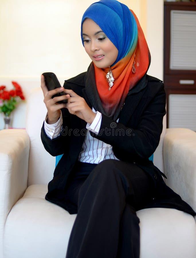 Бизнес-леди Muslimah в головном шарфе с мобильным телефоном стоковое фото