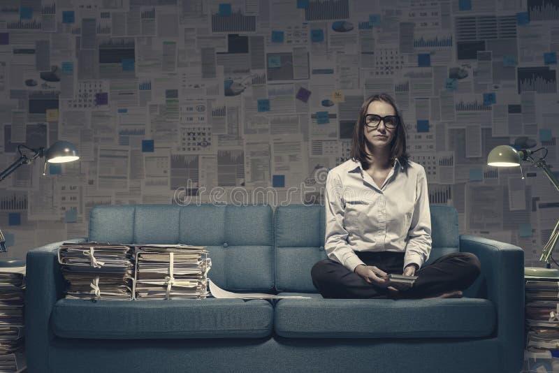 Бизнес-женщина, работающая на диване поздно ночью стоковое фото