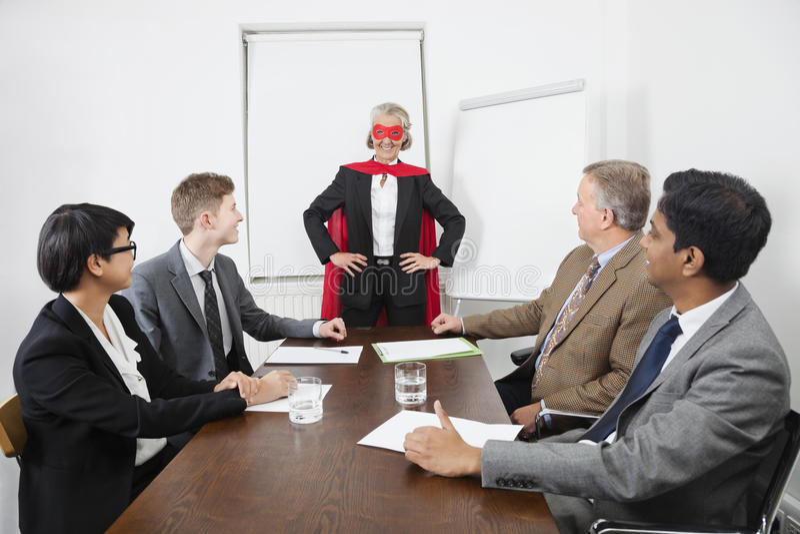 Бизнес лидер как супергерой перед коллегами на встрече в конференц-зале стоковое фото