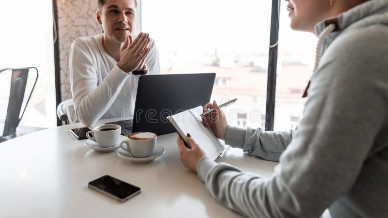 Бизнес-консультант человека говорит женского менеджера о финансовых показателях Женщина делает примечания в тетради показывая про стоковое фото