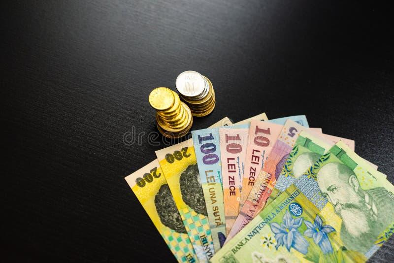 бизнес-концепция, румынская валюта на черном столе Банкноты LEI и монеты стоковые фото
