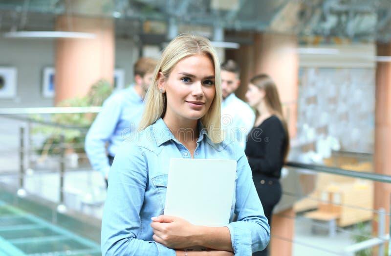 Бизнес-леди в вскользь носке с ее штатом, группа людей в предпосылке на современном ярком офисе стоковые фотографии rf