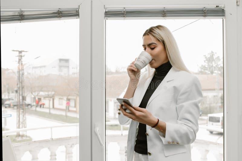 Бизнес-леди в офисе беседуя мобильным телефоном стоковые изображения