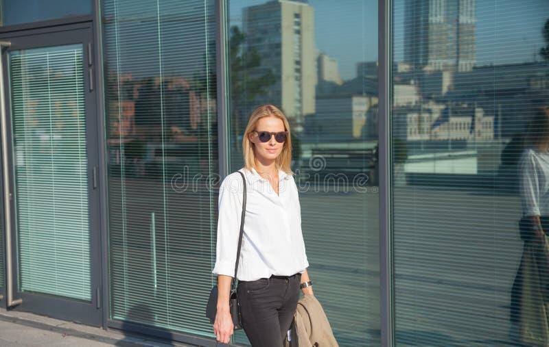 Бизнес-леди в солнечных очках идя на пальто канавы удерживания улицы стоковая фотография