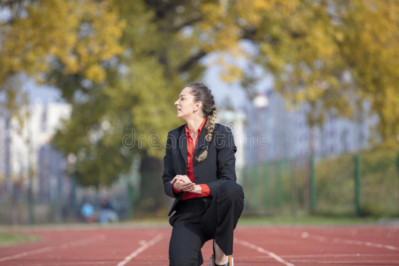 Бизнес-леди в стартовом положении готовом для того чтобы побежать и спринт на гоночном треке атлетики стоковая фотография rf
