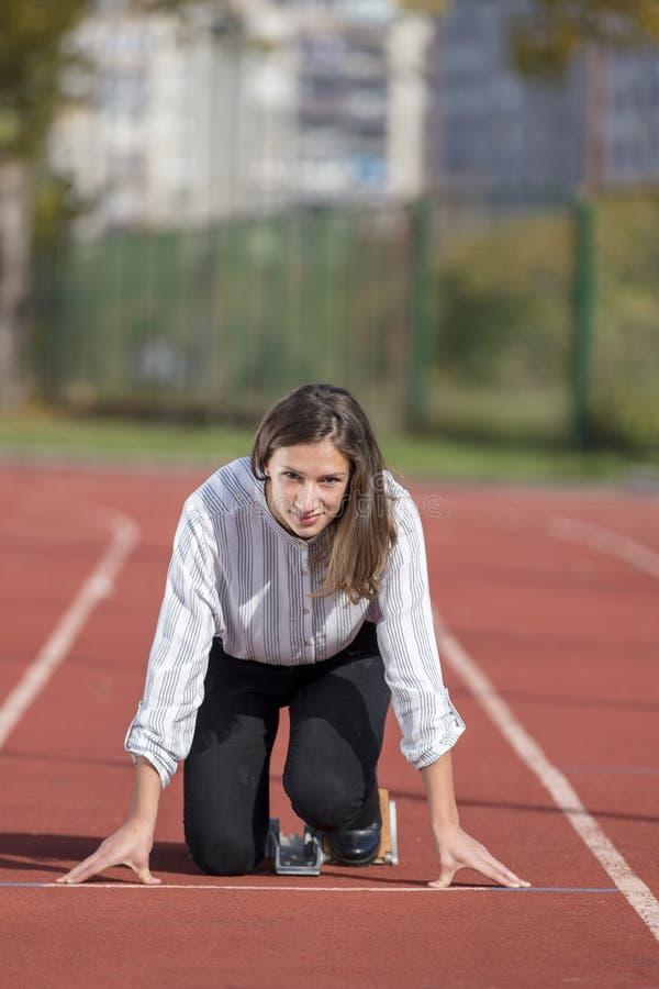 Бизнес-леди в стартовом положении готовом для того чтобы побежать и спринт на гоночном треке атлетики стоковое фото
