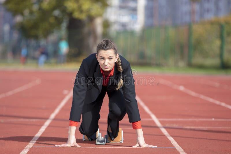Бизнес-леди в стартовом положении готовом для того чтобы побежать и спринт на гоночном треке атлетики стоковые изображения rf