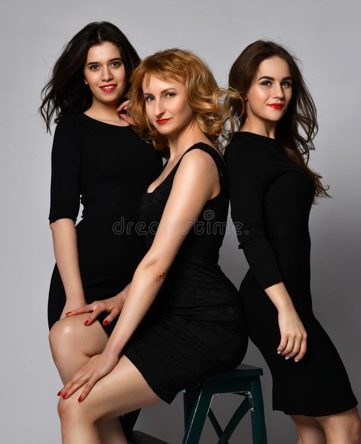 Бизнес-леди 3 в черных платьях имея усмехаться потехи стоковые фотографии rf