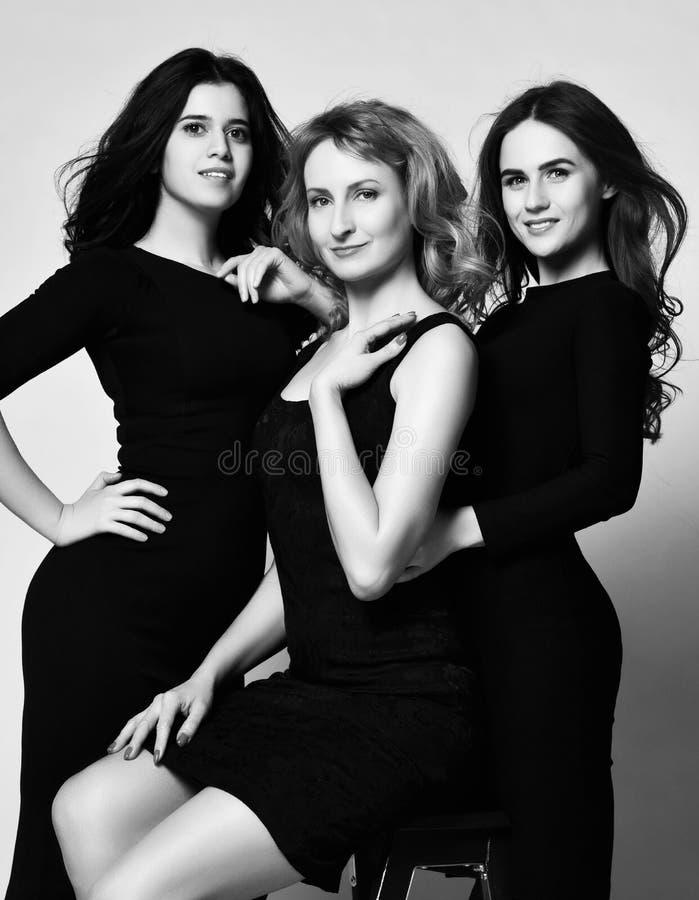 Бизнес-леди 3 в черных платьях имея усмехаться потехи стоковое изображение