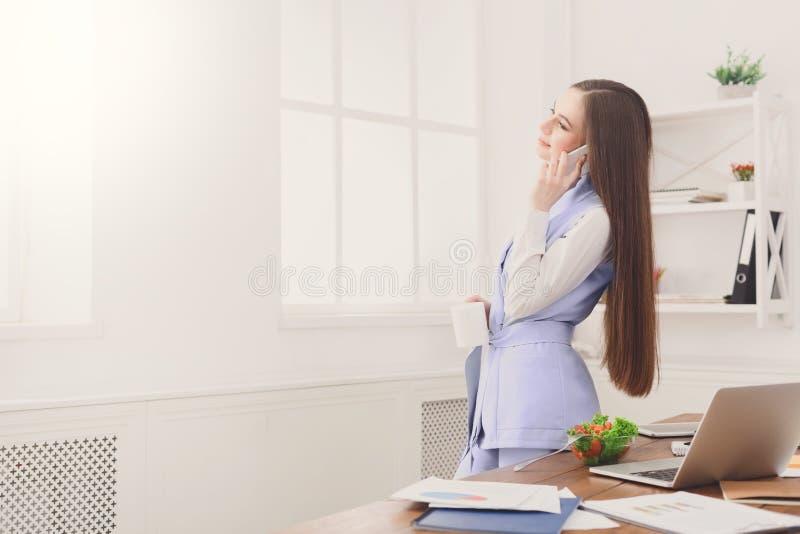 Бизнес-леди говоря на телефоне на окне стоковая фотография rf