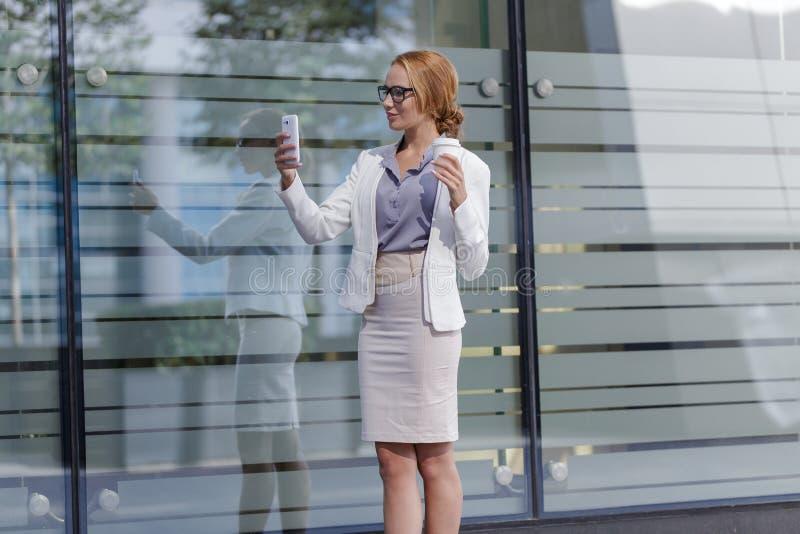 Бизнес-леди держа чашку кофе и принимая selfie на смартфоне стоковые фото