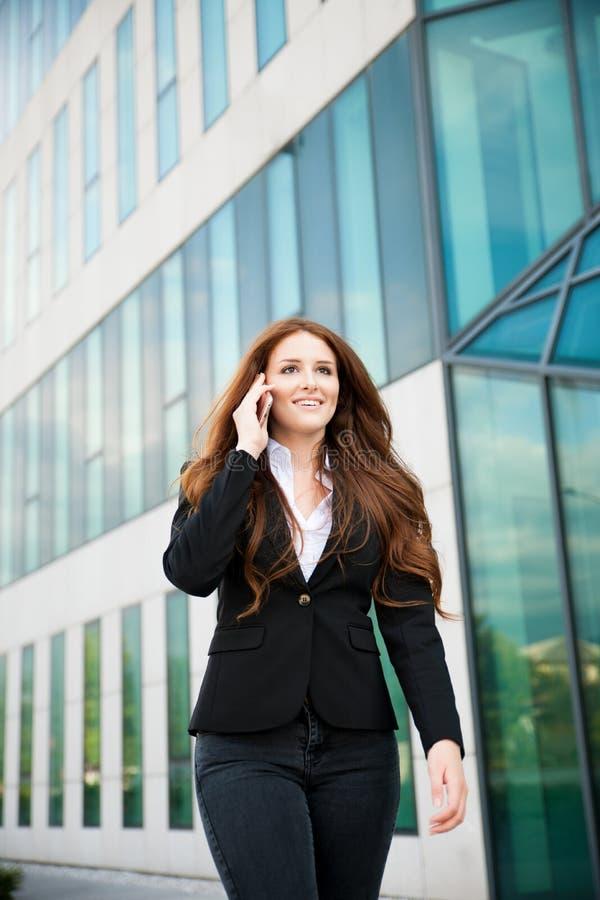 Бизнес-леди идет внешний с smartphone говоря к ее команде стоковое изображение rf