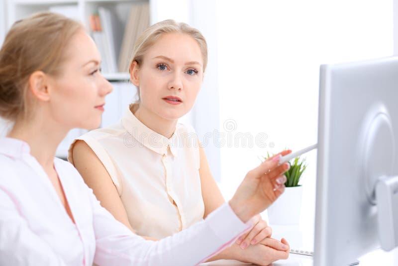 2 бизнес-леди или коллеги обсуждая что-то в офисе Проверка, налог или концепция юриста стоковые фото
