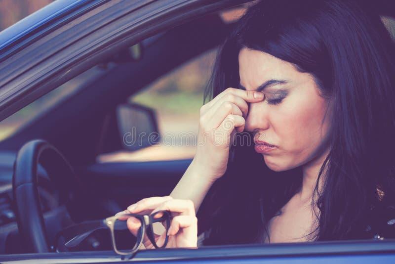 Бизнес-леди имея головную боль принимая ее стекла должна сделать стоп после управлять автомобилем на часе пик стоковые изображения rf