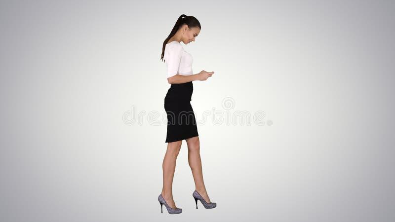 Бизнес-леди используя смартфон и идущ на предпосылку градиента стоковая фотография rf