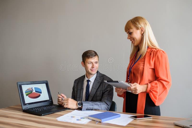 Бизнес-леди и человек на столе офиса работая на проекте стоковое изображение rf