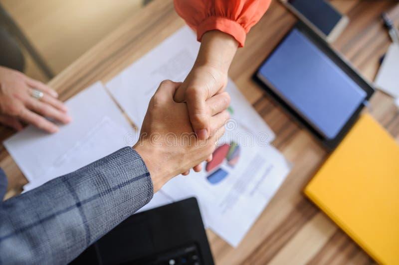 Бизнес-леди и человек на handshaking стола офиса, только руки стоковое фото