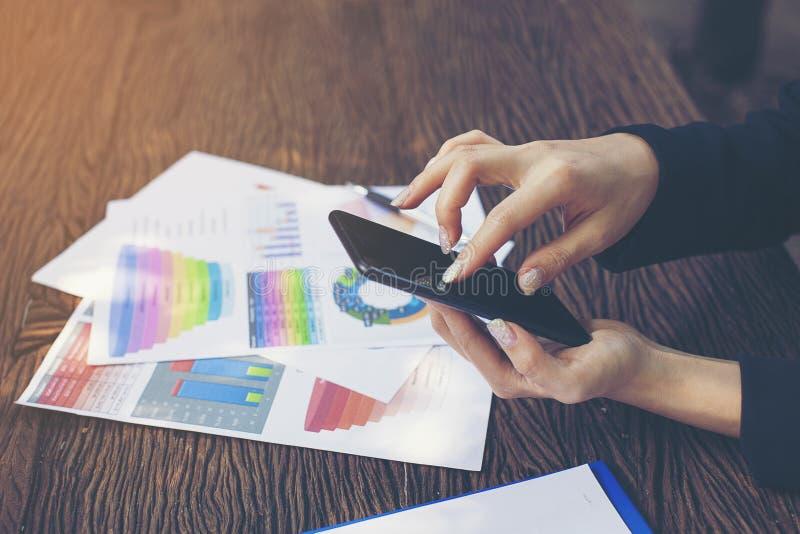 Бизнес-леди касаясь умному телефону для отчетного доклада стоковая фотография