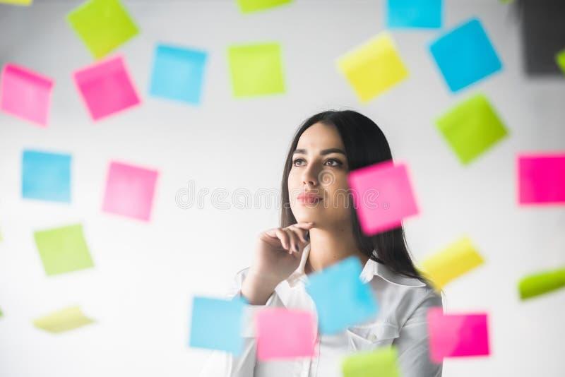 Бизнес-леди клеит стикеры и думать над проектом Думать женщины строгая над стикерами стоковое фото