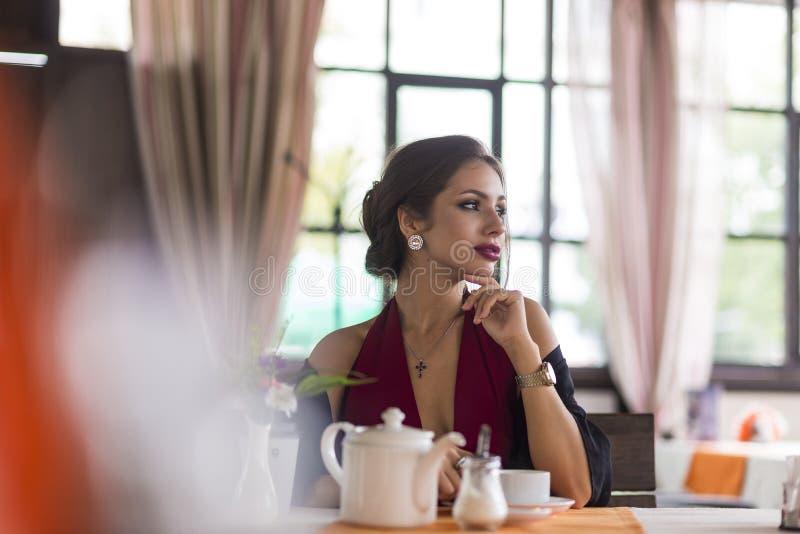Бизнес-леди красивого брюнет кавказская сидя в кафе на ее перерыве на чашку кофе в красном платье стоковая фотография