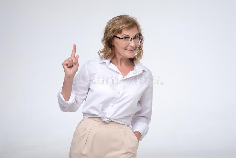 Бизнес-леди красивого среднего возраста зрелая указывая с пальцем вверх по давать совет стоковое изображение rf