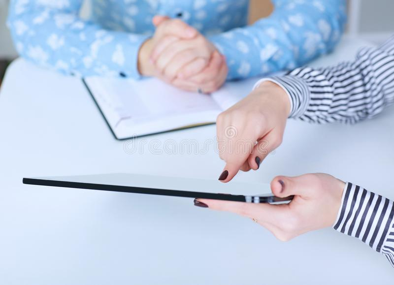 Бизнес-леди показывая цифровую таблетку к сотруднику в офисе Как раз руки над таблицей стоковое изображение
