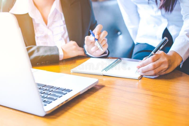 2 бизнес-леди работая в компьютер-книжке и писать дальше стоковое фото