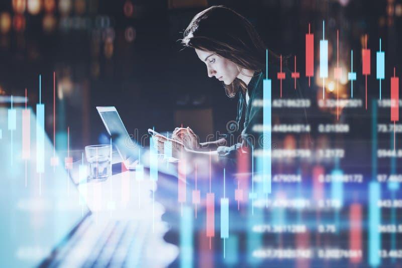 Бизнес-леди сидя вечером офис в переднем ноутбуке с финансовыми диаграммами и используя ее смартфон Красный и стоковые изображения