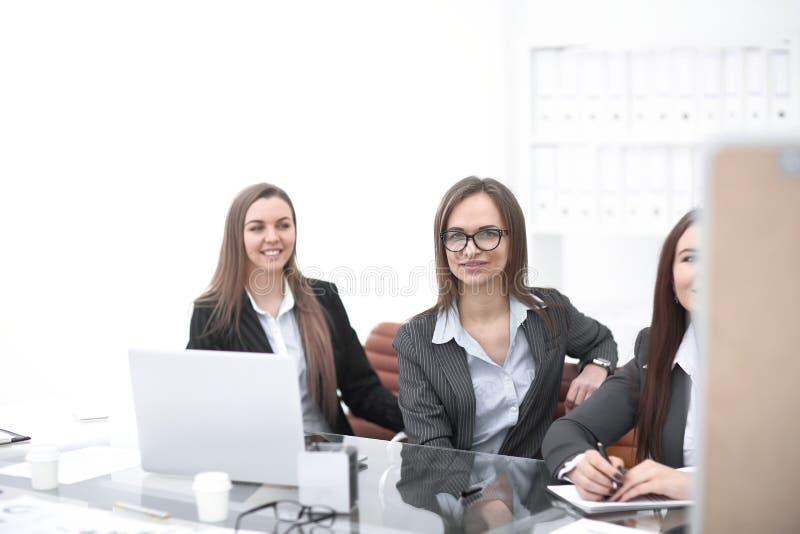 3 бизнес-леди сидя на столе в офисе Фото с космосом экземпляра стоковая фотография