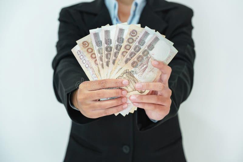 бизнес-леди стоя держащ изолят денег на белой предпосылке стоковая фотография