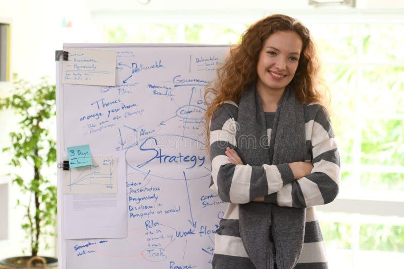 Бизнес-леди стоя на офисе перед диаграммой сальто стоковое фото rf