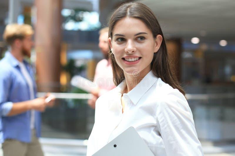 Бизнес-леди с ее штатом, группа людей в предпосылке на современном ярком офисе стоковая фотография