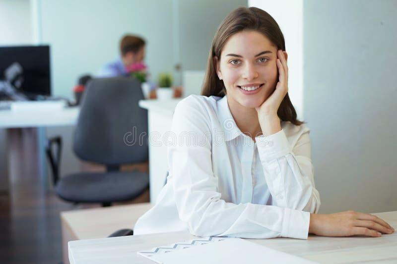 Бизнес-леди с ее штатом, группа людей в предпосылке на современном ярком офисе внутри помещения стоковая фотография