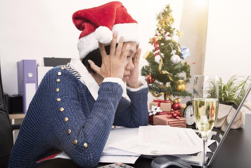 Бизнес-леди с похмельем шляпы santa на офисе стола стоковые фотографии rf