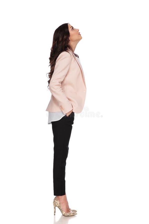 Бизнес-леди с руками в карманн смотрит вверх стоковое фото rf
