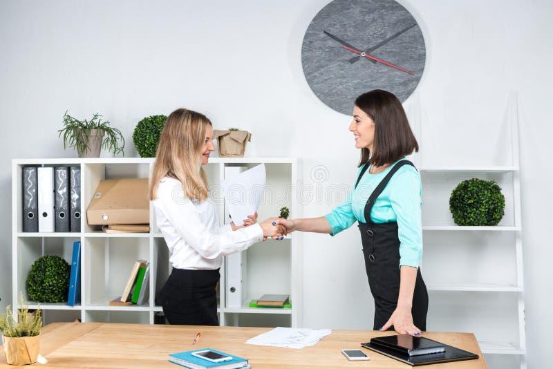 Бизнес-леди темы 2 молодых кавказских делового партнера женщин в официальных одеждах подписывают контракт, делая делом рукопожати стоковые фото