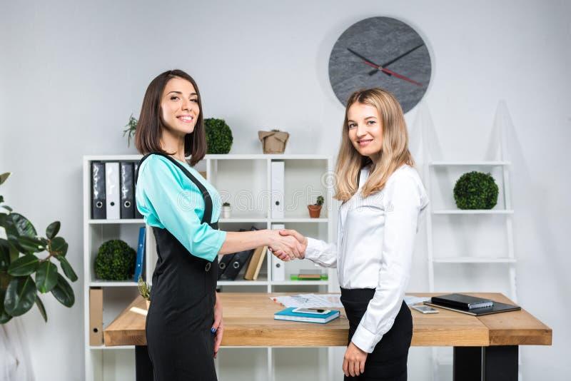 Бизнес-леди темы 2 молодых кавказских делового партнера женщин в официальных одеждах подписывают контракт, делая делом рукопожати стоковые фотографии rf