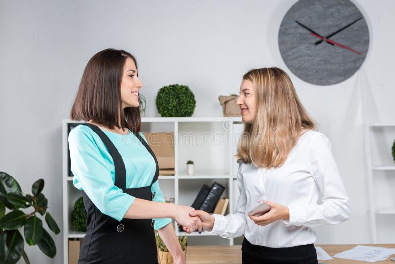 Бизнес-леди темы 2 молодых кавказских делового партнера женщин в официальных одеждах подписывают контракт, делая делом рукопожати стоковая фотография