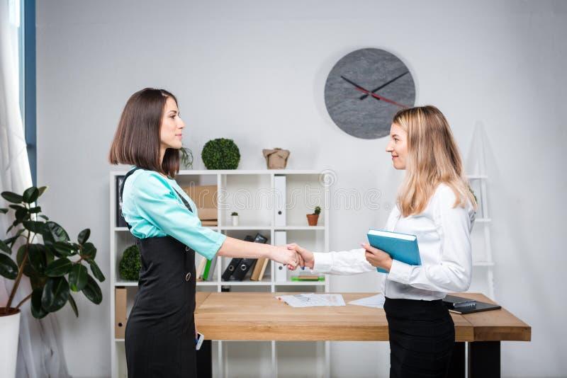 Бизнес-леди темы 2 молодых кавказских делового партнера женщин в официальных одеждах подписывают контракт, делая делом рукопожати стоковые изображения rf