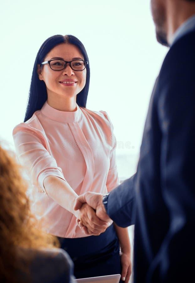 Бизнес-леди тряся руки с партнером стоковое фото rf
